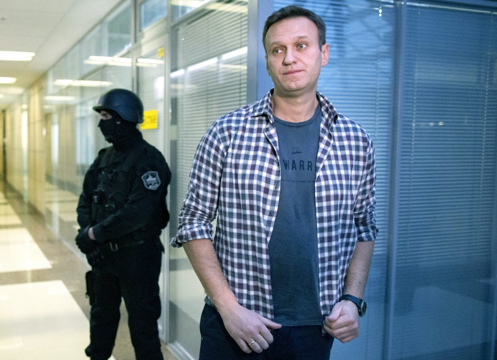 FILE- In this Dec. 26, 2019, file photo, Russian opposition leader Alexei Navalny speaks to the media in front of a security officer standing guard at...