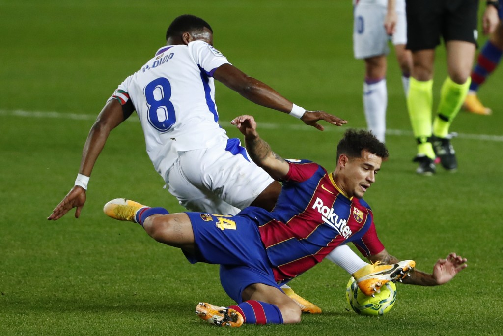 Eibar's Pape Diop, left, challenges Barcelona's Philippe Coutinho during the Spanish La Liga soccer match between Barcelona and Eibar at the Camp Nou ...