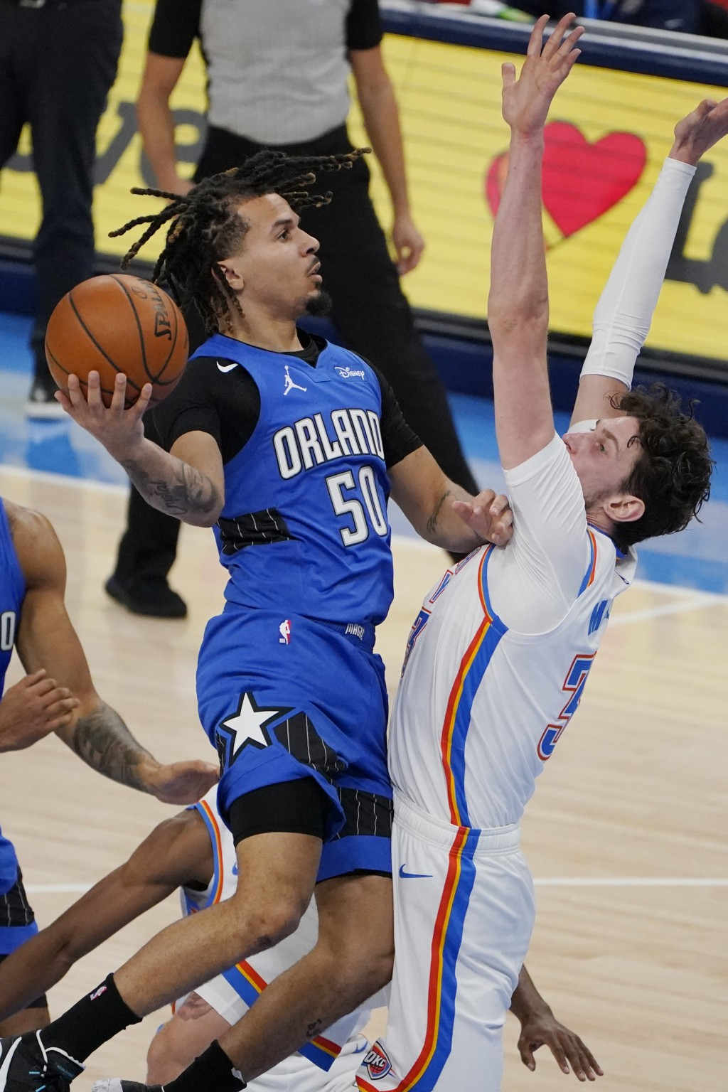 Orlando Magic guard Cole Anthony (50) goes to the basket past Oklahoma City Thunder forward Mike Muscala, right, in the first half of an NBA basketbal...