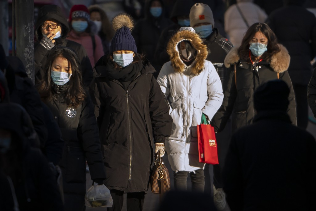 People wearing face masks to protect against the spread of the coronavirus walk along a street during the morning rush hour in Beijing, Wednesday, Dec...