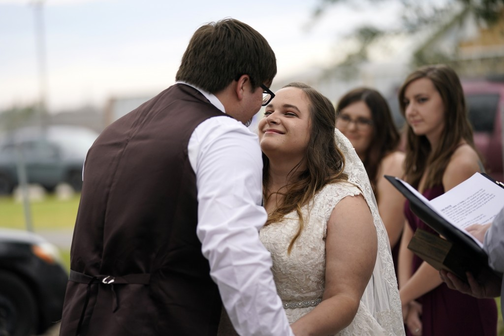 Emily and Taylor Pascale kiss after exchanging vows at their wedding outside the home of Taylor's parents, Friday, Dec. 4, 2020, in Grand Lake, La., w...