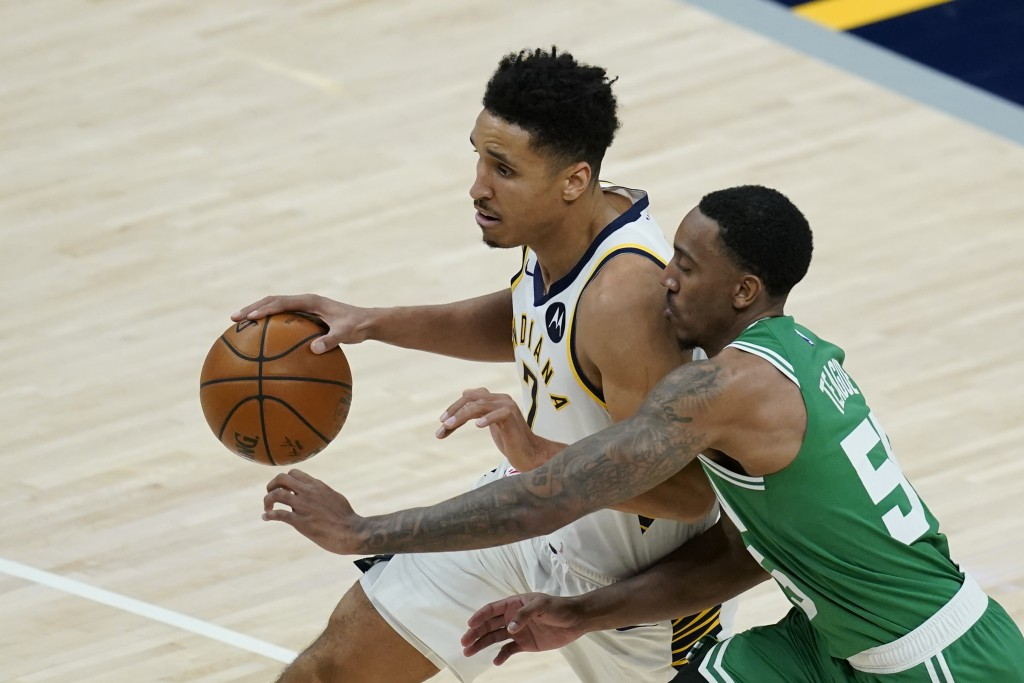 Indiana Pacers' Malcolm Brogdon (7) is defended by Boston Celtics' Jeff Teague (55) during the second half of an NBA basketball game Tuesday, Dec. 29,...
