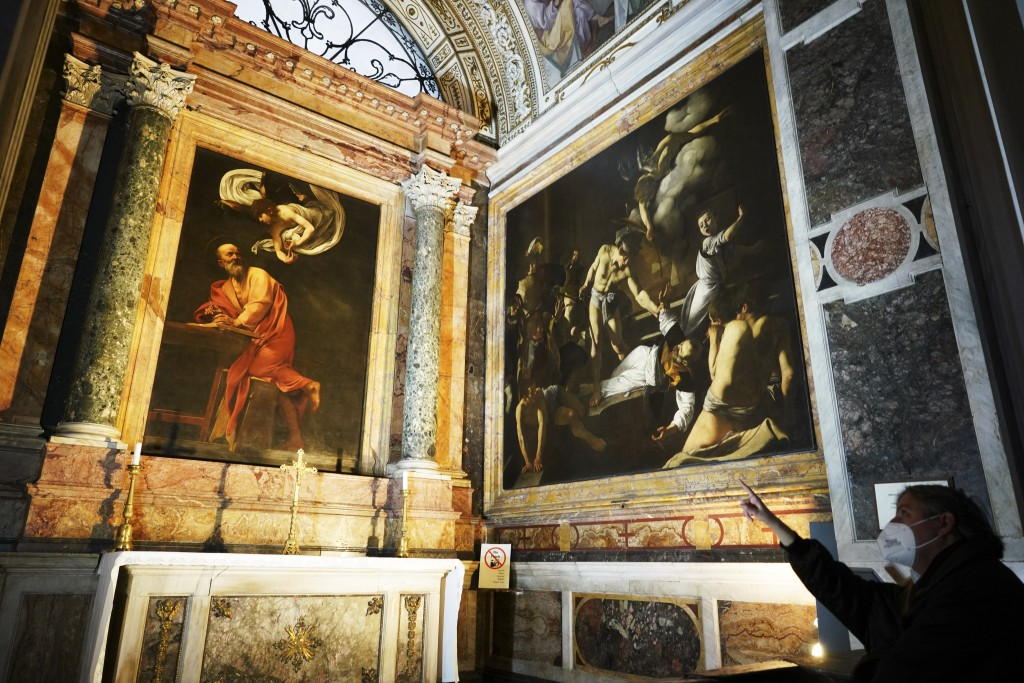 A woman wearing a face mask to curb the spread of COVID-19 points to a cycle of paintings by 16th century artist Michelangelo Merisi, known as Caravag...