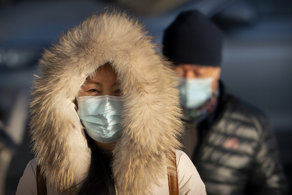 A woman wearing a face mask to protect against the spread of the coronavirus walks along a street during the morning rush hour in Beijing, Wednesday, ...