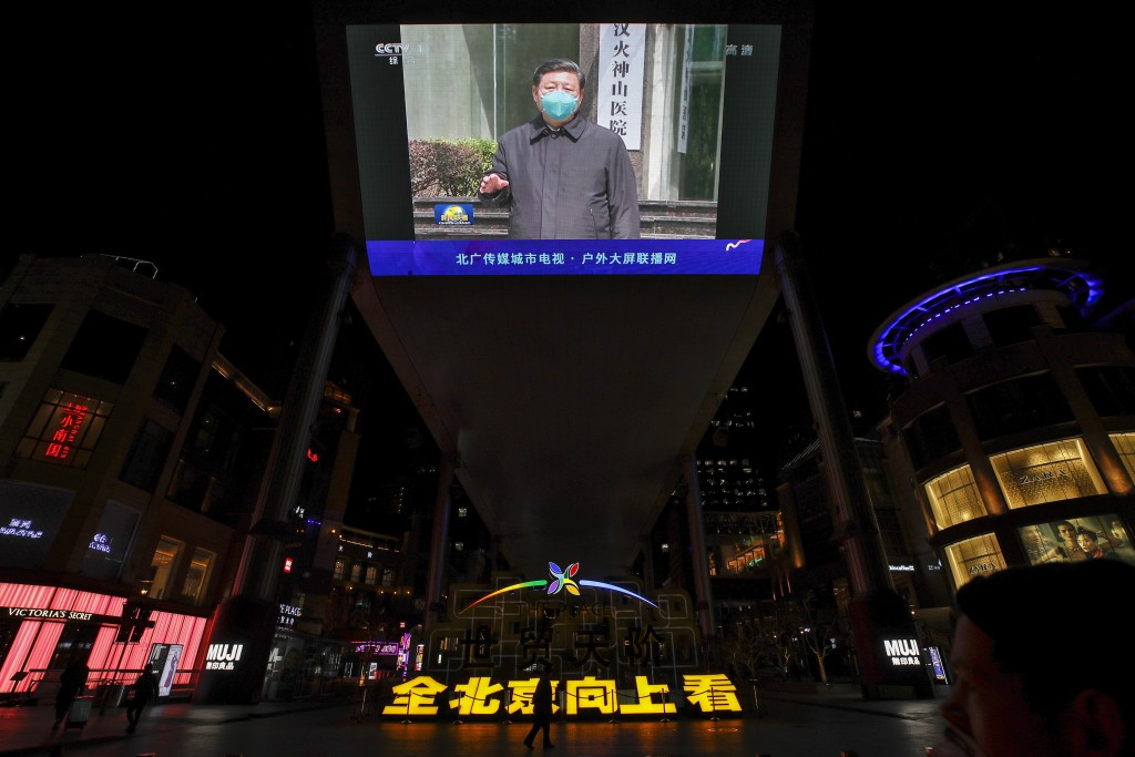 FILE - In this Tuesday, March 10, 2020 file photo, people walk by a giant TV screen at a quiet shopping mall in Beijing broadcasting news of Chinese P...