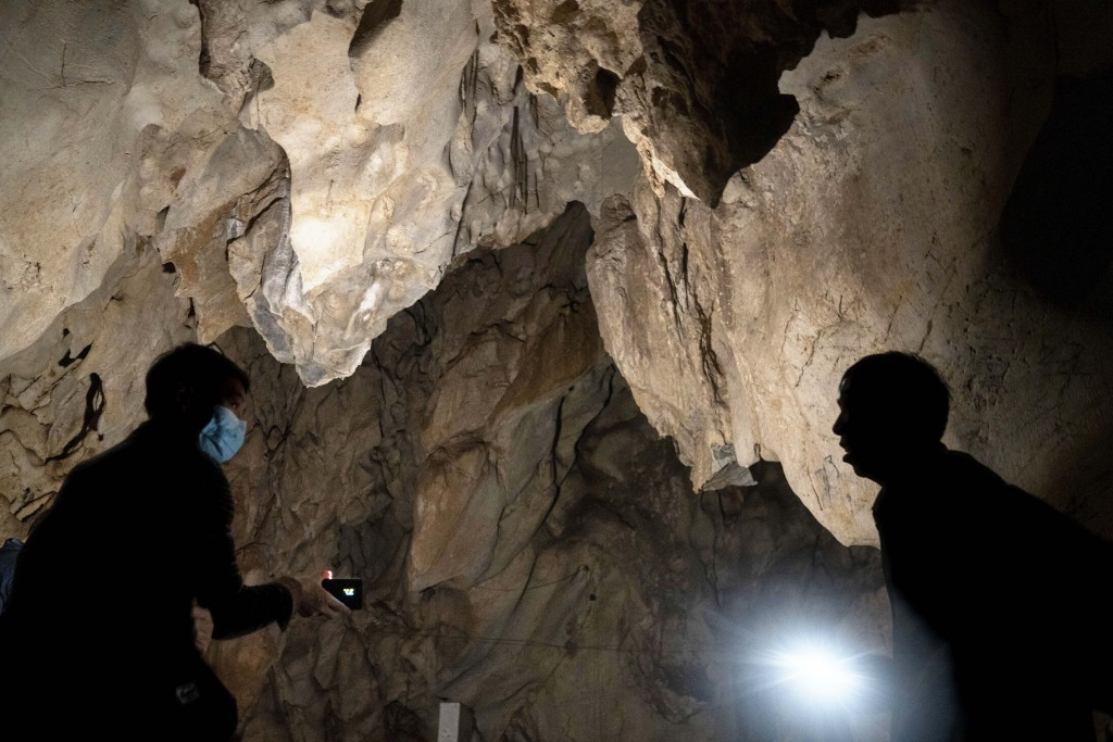 Visitors look inside the abandoned Wanling cave near Manhaguo village in southern China's Yunnan province on Wednesday, Dec. 2, 2020. Villagers said t...