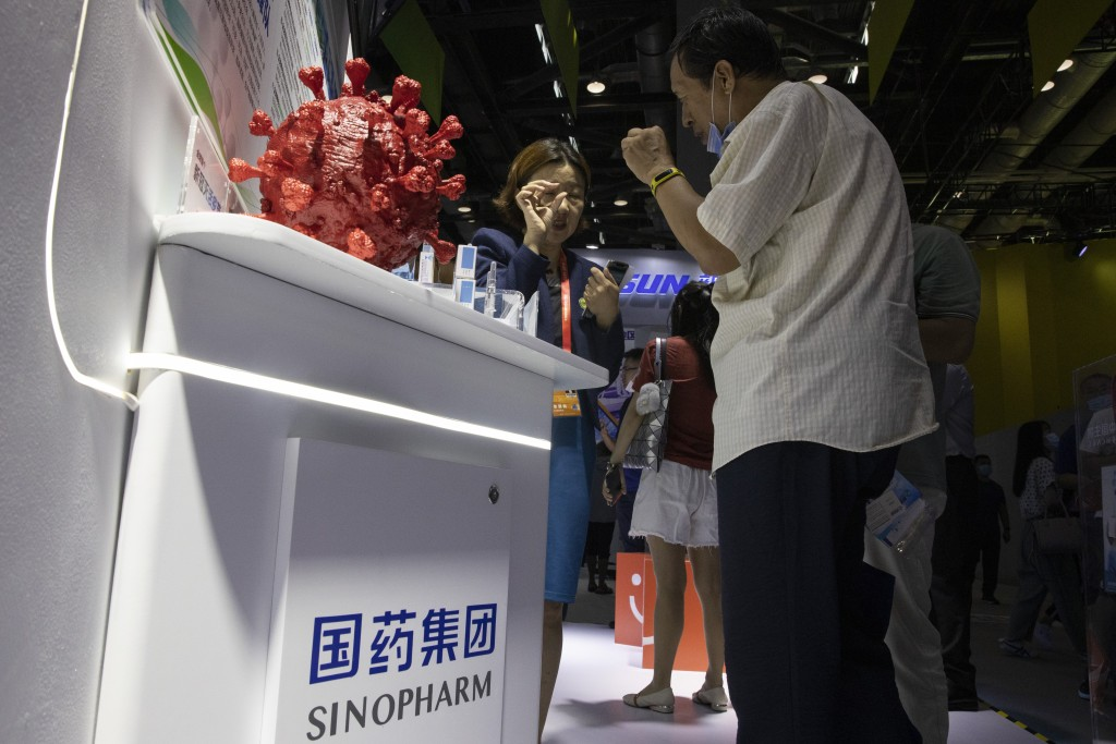 A promoter talks about the COVID-19 vaccine produced by Sinopharm subsidiary CNBG during a trade fair in Beijing on Sunday, Sept. 6, 2020. The Chinese...