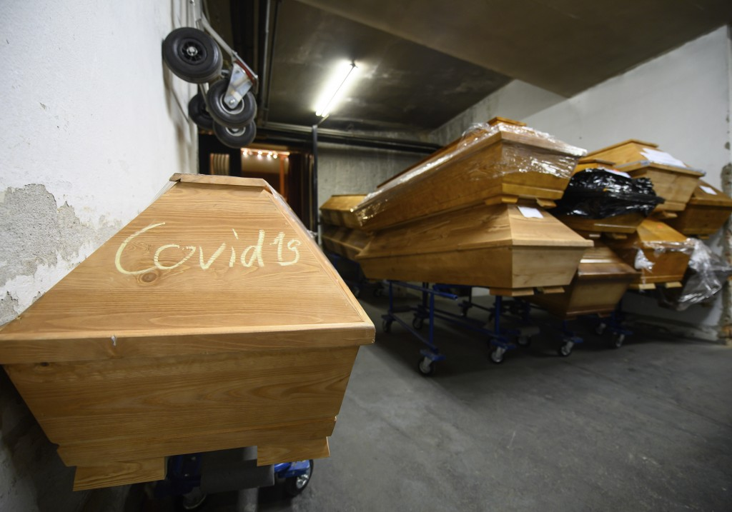 FILE - In this Tuesday, Dec. 22, 2020 file photo, the word 'Covid 19' is written in chalk on a coffin containing a deceased person who died of or with...