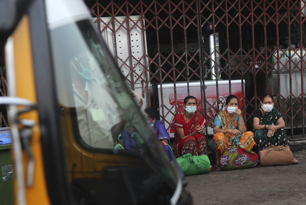A group of women wearing face masks as a precaution against the coronavirus waits for transport in Dharavi, one of Asia's biggest slums, in Mumbai, In...