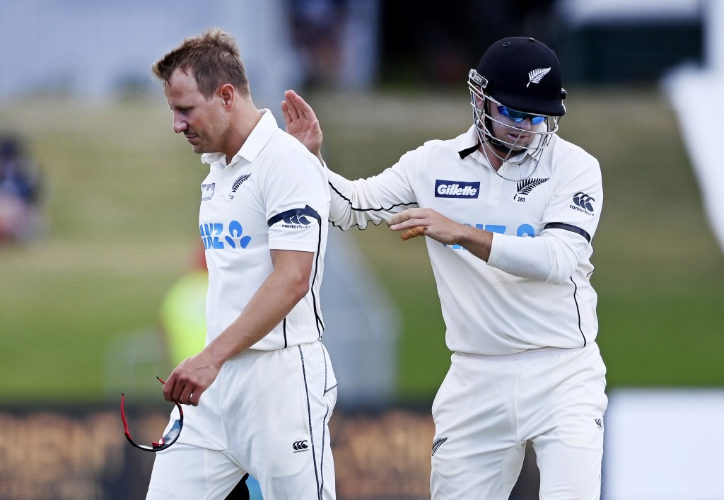 New Zealand's injured bowler Neil Wagner, left, is consoled by teammate Tom Latham as he leaves the field during play on the final day of the first cr...