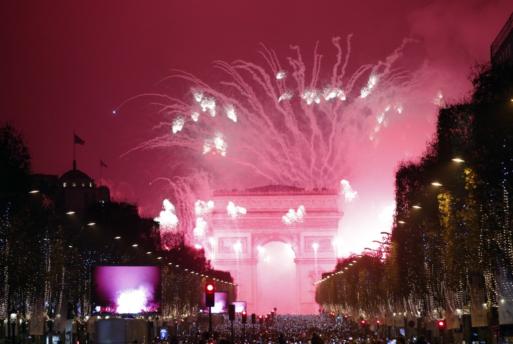 FILE - In this Jan. 1, 2017, file photo, fireworks illuminate the Arc de Triomphe during the New Year's Eve celebration on the Champs Elysees, in Pari...