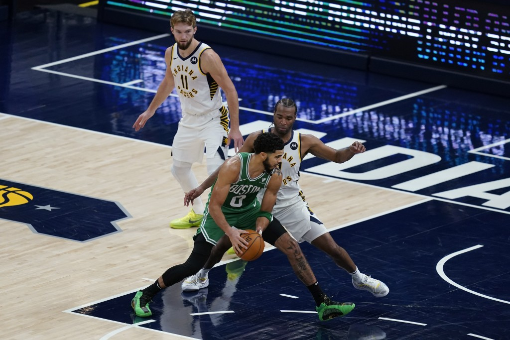 Boston Celtics' Jayson Tatum (0) goes to the basket against Indiana Pacers' T.J. Warren, right, during the second half of an NBA basketball game Tuesd...