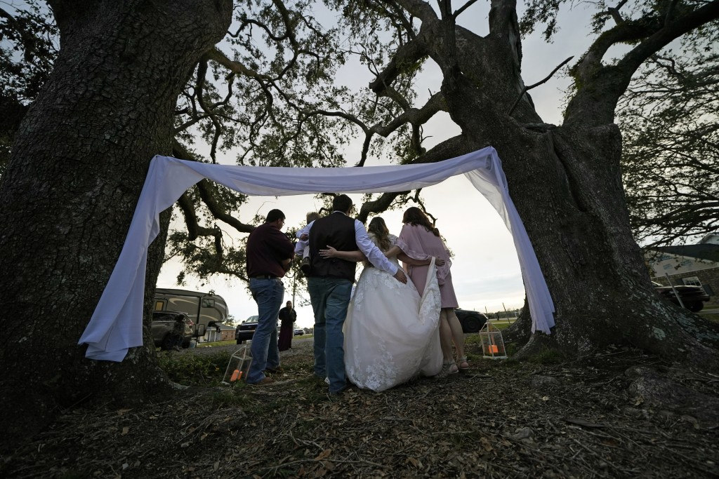 Emily and Taylor Pascale pose for photos after getting married outside the home of Taylor's parents, Friday, Dec. 4, 2020, in Grand Lake, La., which w...