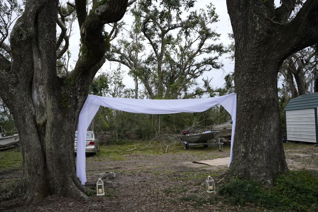 Damaged trees and debris are seen at the wedding site for Emily and Taylor Pascale, outside Taylor's parent's home, Friday, Dec. 4, 2020, in Grand Lak...