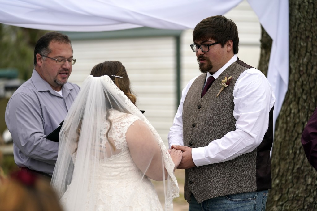 Minister Scotty Poole officiates the wedding of Emily and Taylor Pascale outside the home of Taylor's parents, Friday, Dec. 4, 2020, in Grand Lake, La...