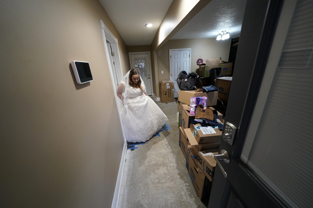 Emily Pascale walks past boxes to get married, inside the home of Emily's now in-laws, Friday, Dec. 4, 2020, in Grand Lake, La., which was heavily dam...