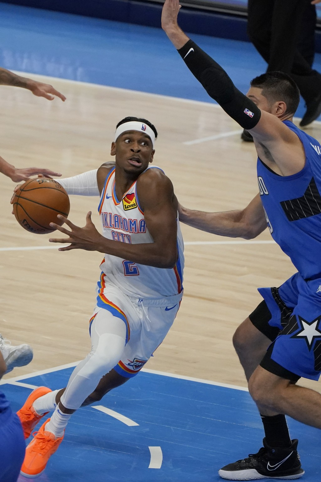 Oklahoma City Thunder guard Shai Gilgeous-Alexander (2) drives around Orlando Magic center Nikola Vucevic during the second half of an NBA basketball ...