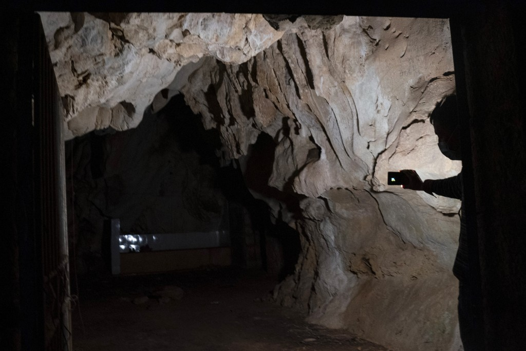 A man shines a light in the abandoned Wanling cave near Manhaguo village in southern China's Yunnan province on Wednesday, Dec. 2, 2020. Villagers sai...