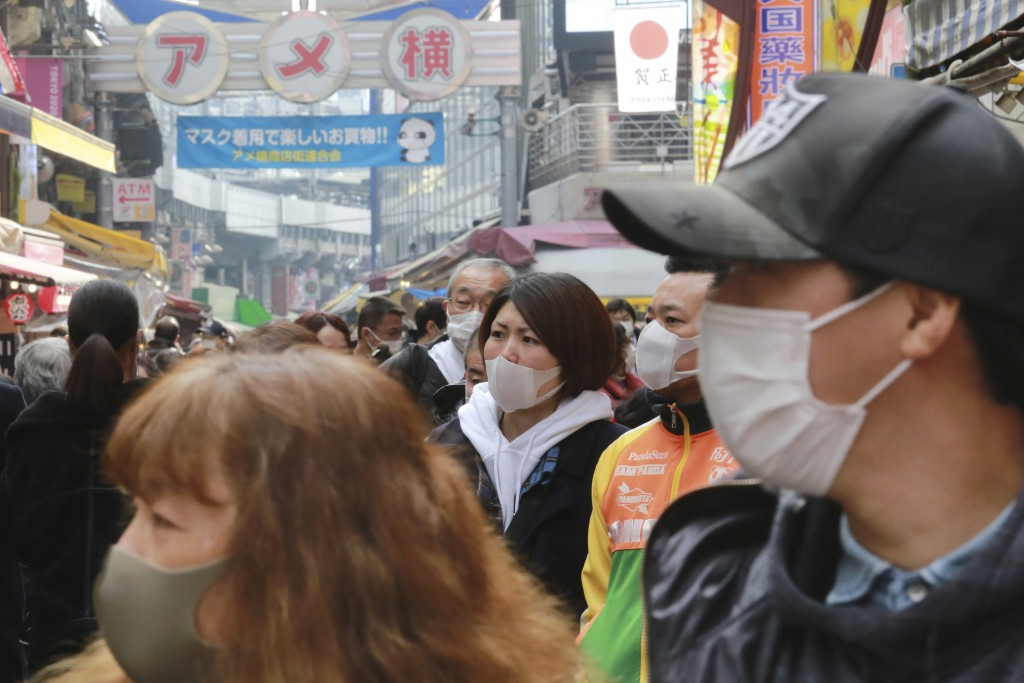 People wearing face masks to protect against the spread of the coronavirus visit the Ameyoko shopping street in Tokyo, Wednesday, Dec. 30, 2020. (AP P...