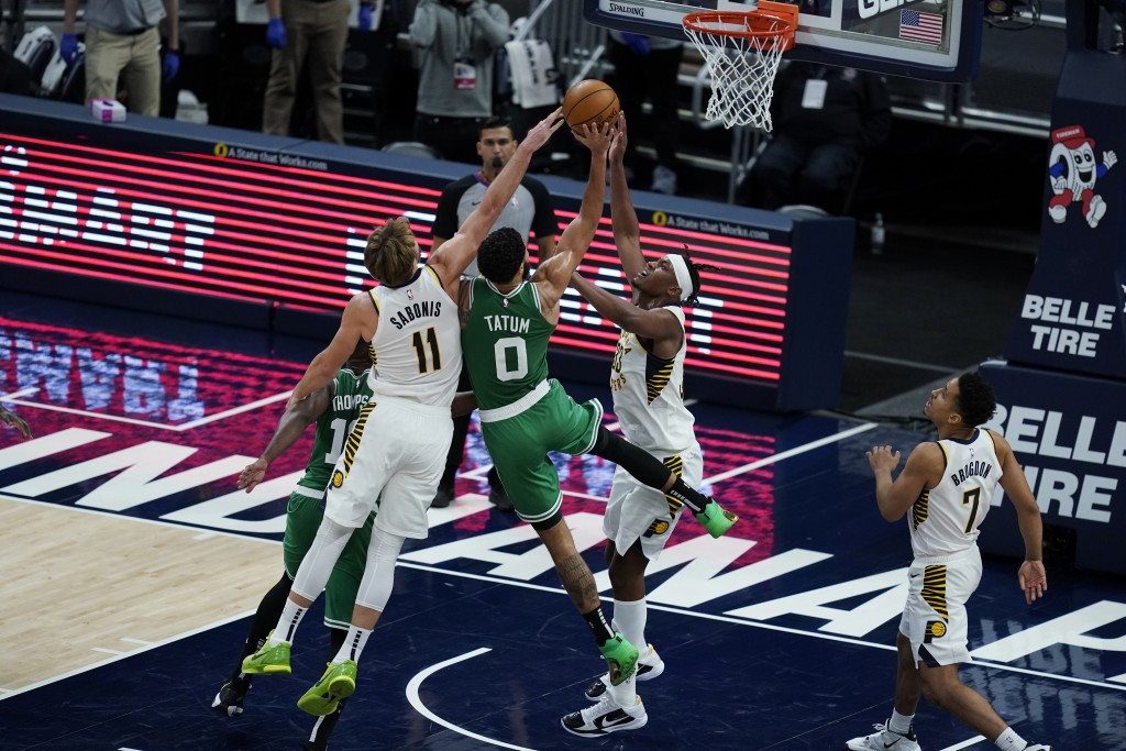 Boston Celtics' Jayson Tatum (0) shoots between Indiana Pacers' Domantas Sabonis (11) and Myles Turner (33) during the second half of an NBA basketbal...