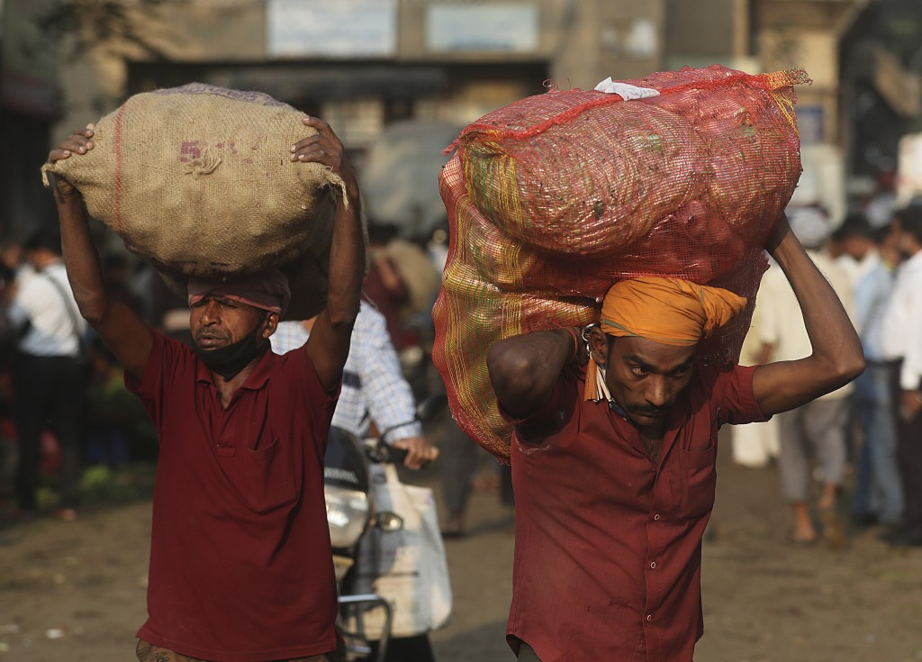 Laborers carry vegetables in Mumbai, India, Wednesday, Dec. 30, 2020. India's confirmed coronavirus cases have crossed 10 million with new infections ...