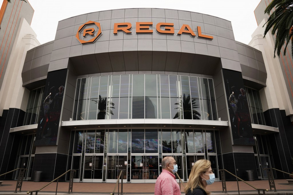 FILE - In this Sept. 8, 2020, file photo, two shoppers in face masks due to the coronavirus pandemic walk past a Regal movie theater in Irvine, Calif....