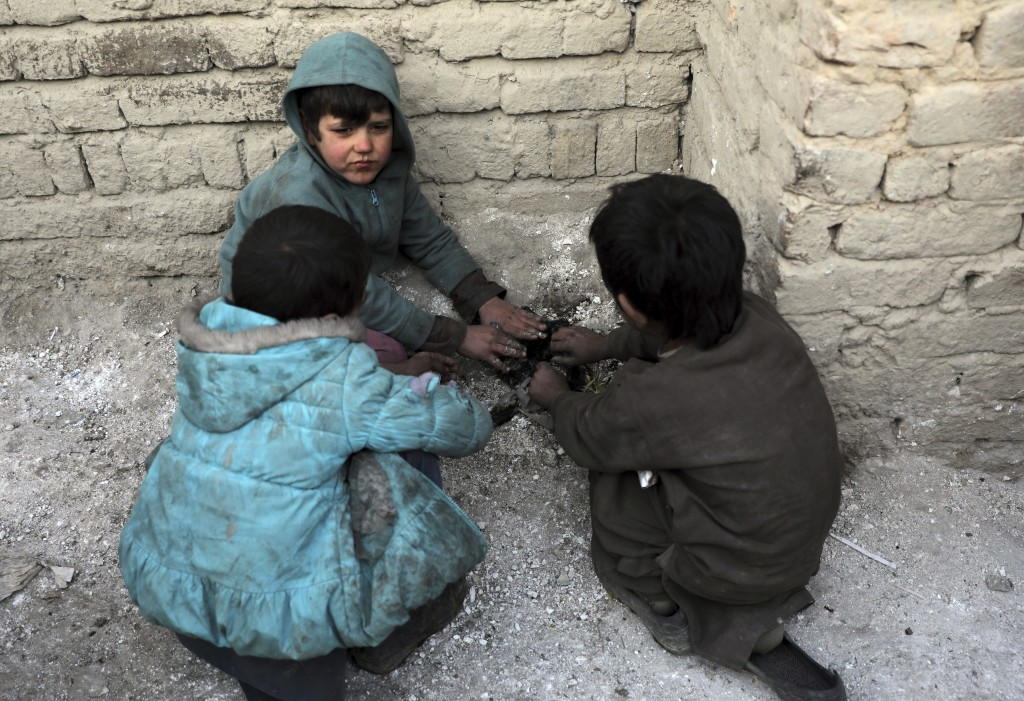Internally displaced boys warm themselves near a fire outside their temporary home in the city of Kabul, Afghanistan, Wednesday, Dec. 30, 2020. Save t...