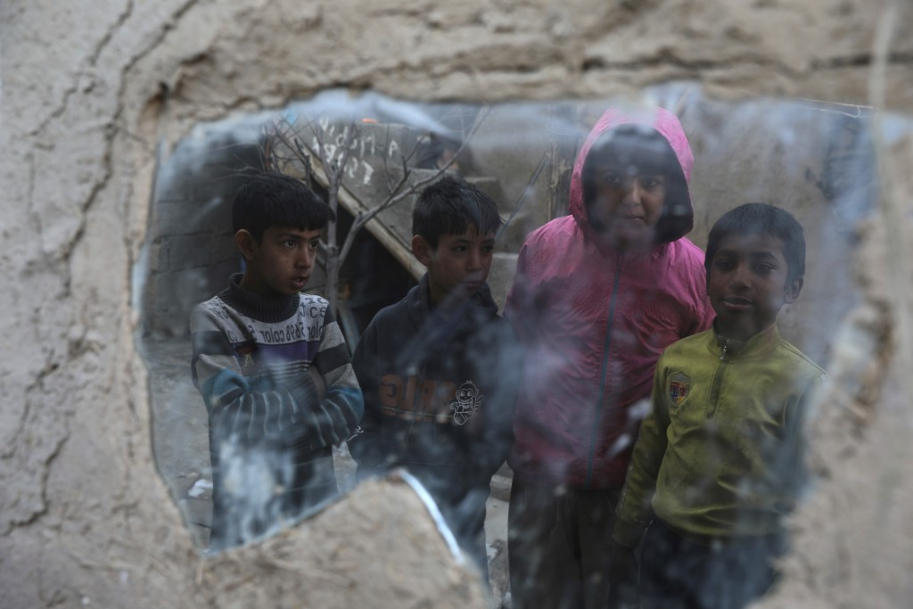 Internally displaced boys are reflected in a mirror inside their temporary home in the city of Kabul, Afghanistan, Wednesday, Dec. 30, 2020. Save the ...