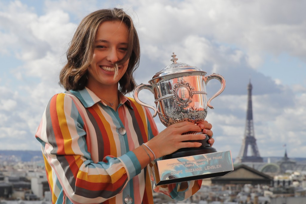FILE - Poland's Iga Swiatek, poses with the French Open women's singles trophy on a rooftop with the Eiffel Tower in the background in Paris, in this ...