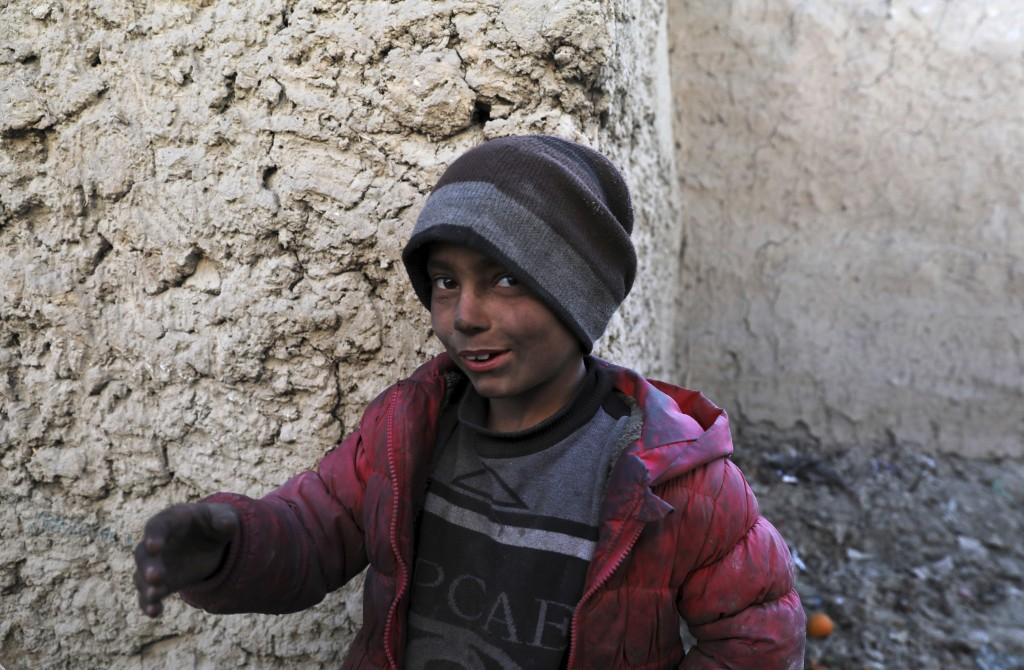 An internally displaced boy poses for a photograph outside his temporary home in the city of Kabul, Afghanistan, Wednesday, Dec. 30, 2020. Save the Ch...