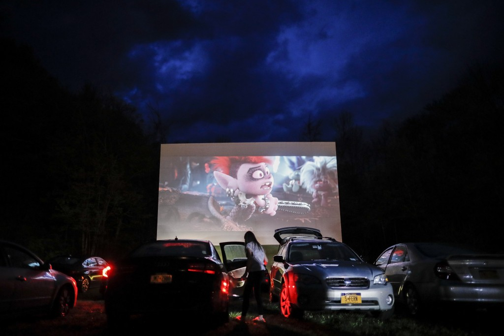 """FILE - In this Friday, May 15, 2020, file photo, guests watch a showing of """"Trolls World Tour,"""" at the Four Brothers Drive In Theatre amid the coronav..."""