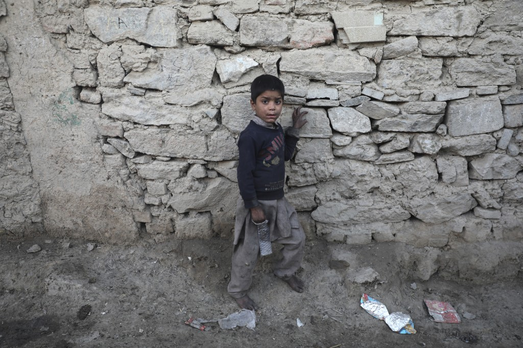 An internally displaced boy pose for a photograph outside his temporary home in the city of Kabul, Afghanistan, Wednesday, Dec. 30, 2020. Save the Chi...