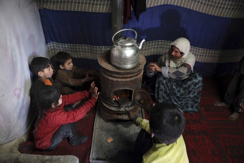 Internally displaced children sit around a stove to keep warm in a temporary shelter in the city of Kabul, Afghanistan, Wednesday, Dec. 30, 2020. Save...