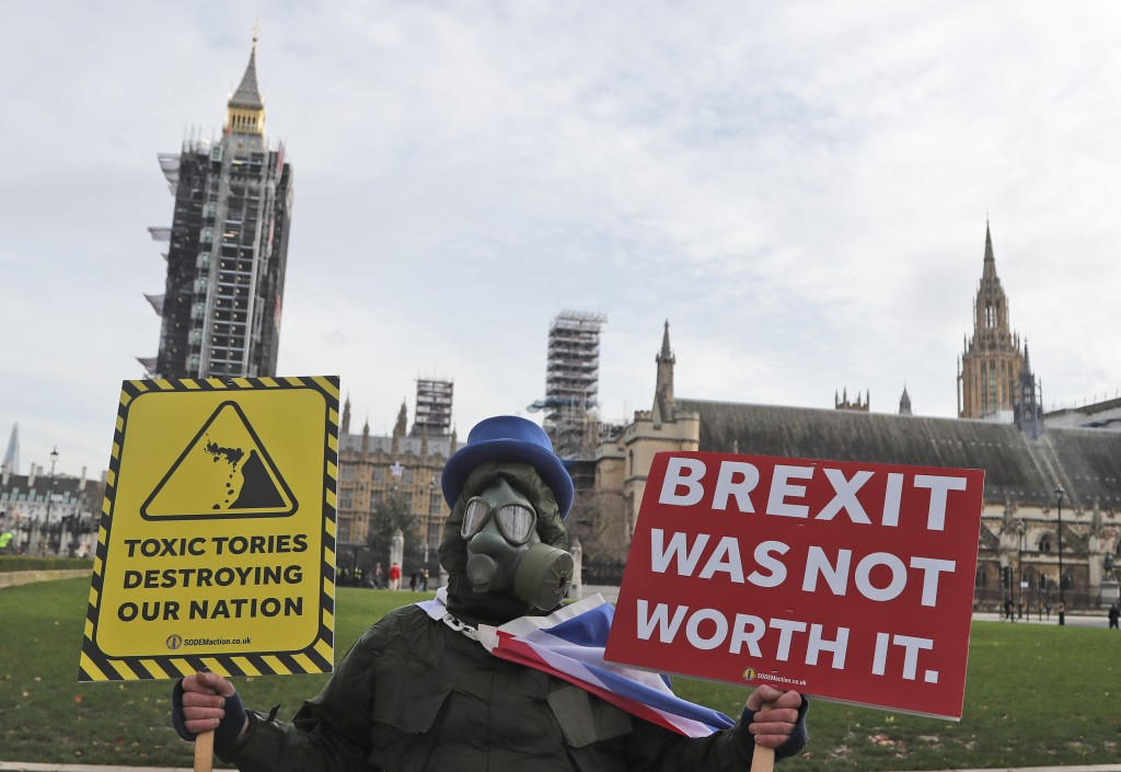 FILE - In this Wednesday, Dec. 30, 2020 file photo, a pro EU protestor stands in parliament square in front of Parliament during the debate in the Hou...