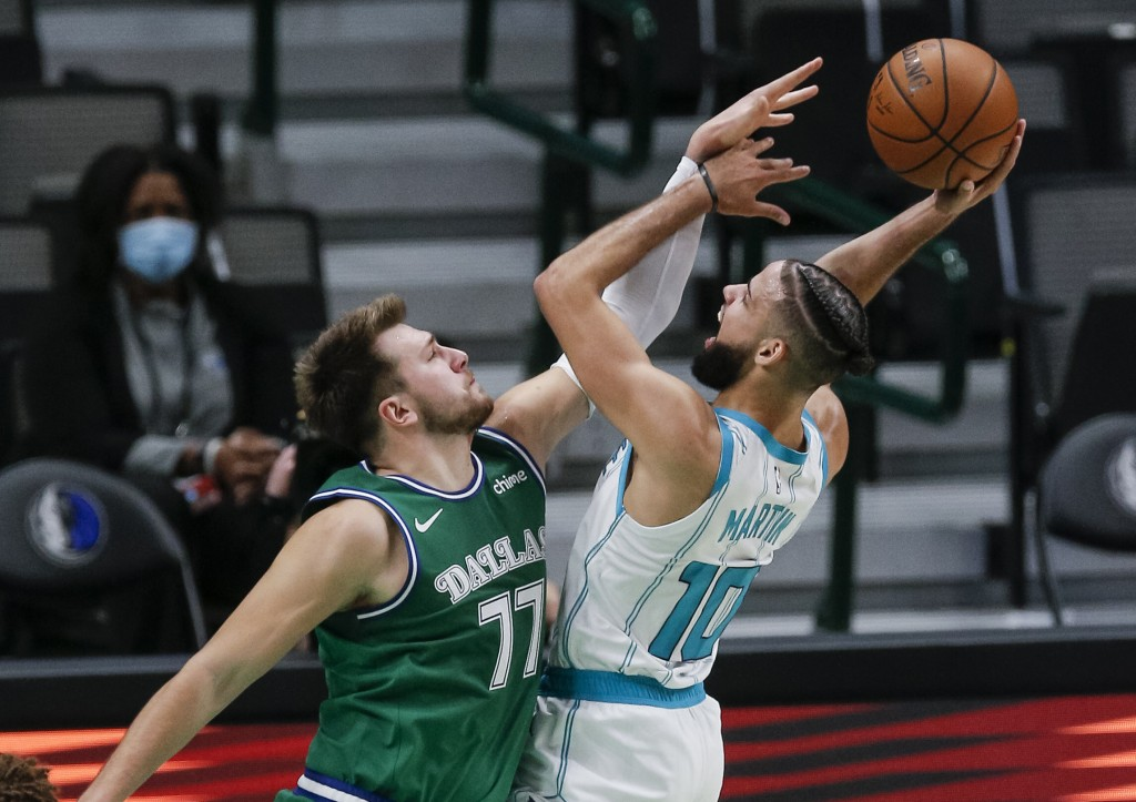 Charlotte Hornets forward Caleb Martin (10) attempts a shot as Dallas Mavericks guard Luka Doncic (77) defends during the first half of an NBA basketb...