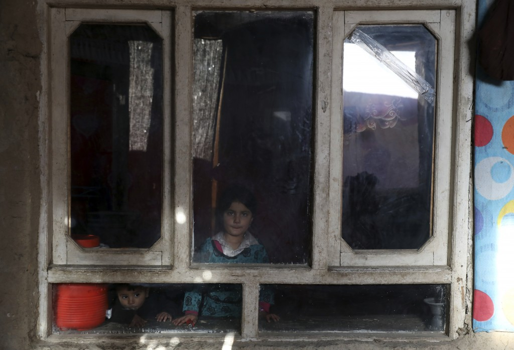 An internally displaced sister and brother pose for a photograph inside their temporary home in the city of Kabul, Afghanistan, Wednesday, Dec. 30, 20...