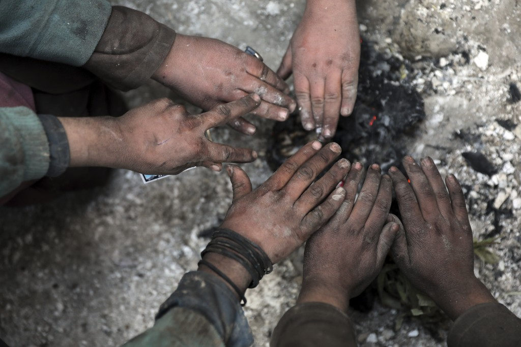 Internally displaced boys warm themselves near a fire outside of their temporary home in the city of Kabul, Afghanistan, Wednesday, Dec. 30, 2020. Sav...