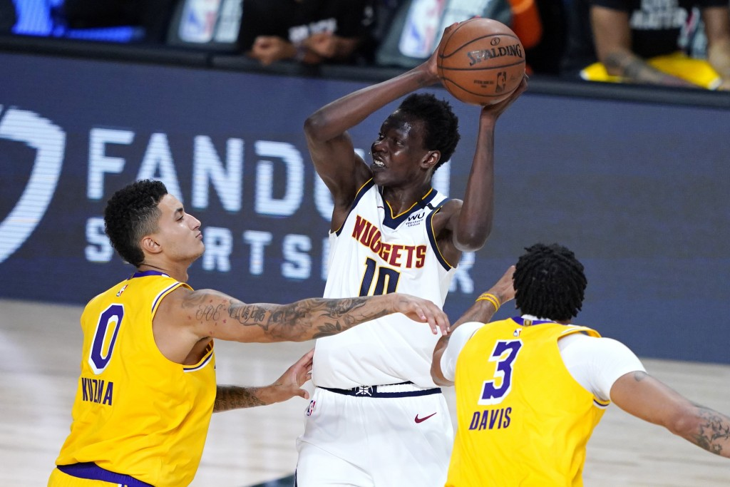 FILE - Denver Nuggets' Bol Bol (10) is pressured by Los Angeles Lakers' Kyle Kuzma (0) and Anthony Davis (3) during the second half of an NBA basketba...