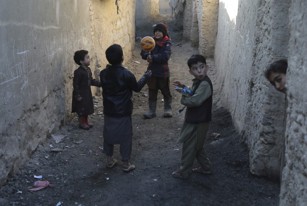 Internally displaced boys play with a ball outside their temporary home in the city of Kabul, Afghanistan, Wednesday, Dec. 30, 2020. Save the Children...