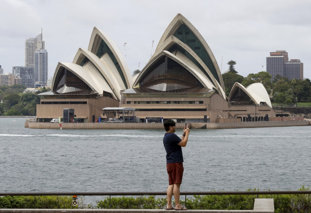 A man films the harbour foreshore on his mobile phone ahead of New Years Eve in Sydney, Australia, Thursday, Dec. 31, 2020. One million people would u...
