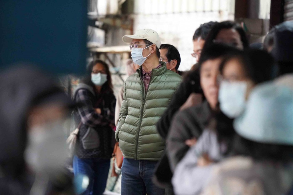 People are in a queue waiting for buying masks in front of a drugstore in Taipei City.