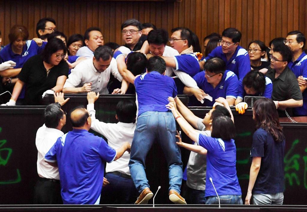 國民黨立委(藍衣)29日占領立法院議場,民進黨立委隨後攻入議場,雙方在主席台前爆發肢體衝突,互相推擠亂成一團。