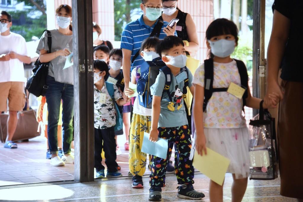 開學後校園為配合防疫政策,實施量體溫、酒精手部消毒等防疫措施,多數學生也主動戴上口罩上學。(圖/中央社)