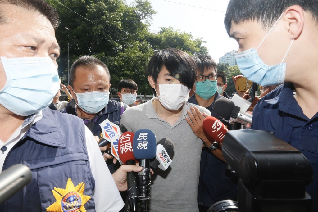Lo (center) surrounded by reporters.