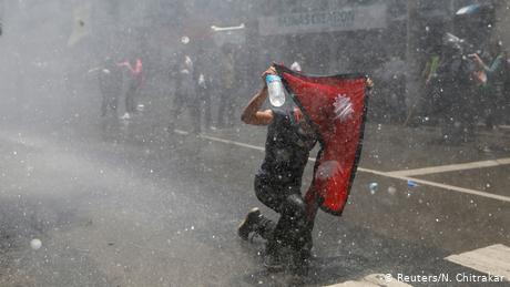 A youth holding the national flag of Nepal braves the water cannon during an anti-government protest in June