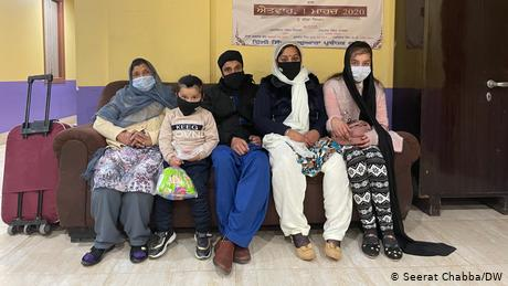 A family waits at a Sikh temple in New Delhi after landing in India from Kabul