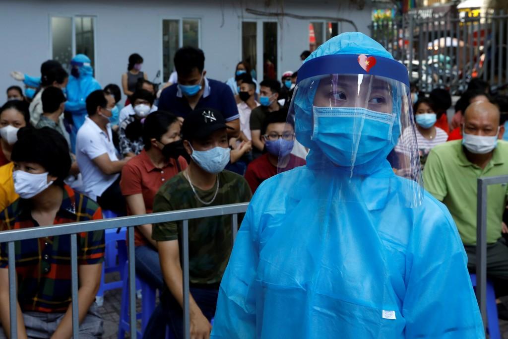 Healthcare worker walks past as local residents wait at COVID-19testingcenterinHanoi,Vietnam. (Reuters photo)