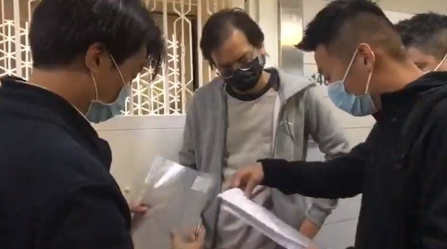 Hong Kong police showing documents to StandNews editor-in-chief Chung Pui-kuen. (Facebook, StandNews livestream screenshot)