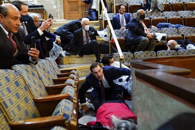 國會大廈遭暴徒攻擊時, 眾議院內驚恐萬狀, 議員們紛紛尋找掩護 (美聯社)