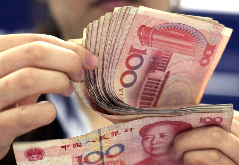 Bank clerk counts Chinese 100 Yuan notes in Shanghai.